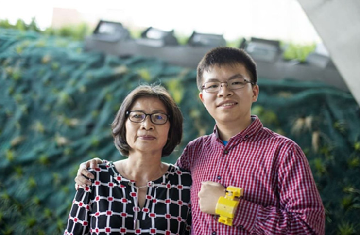 Frank Nguyen's mother (left) and Frank Nguyen (right) wearing the first device he created.