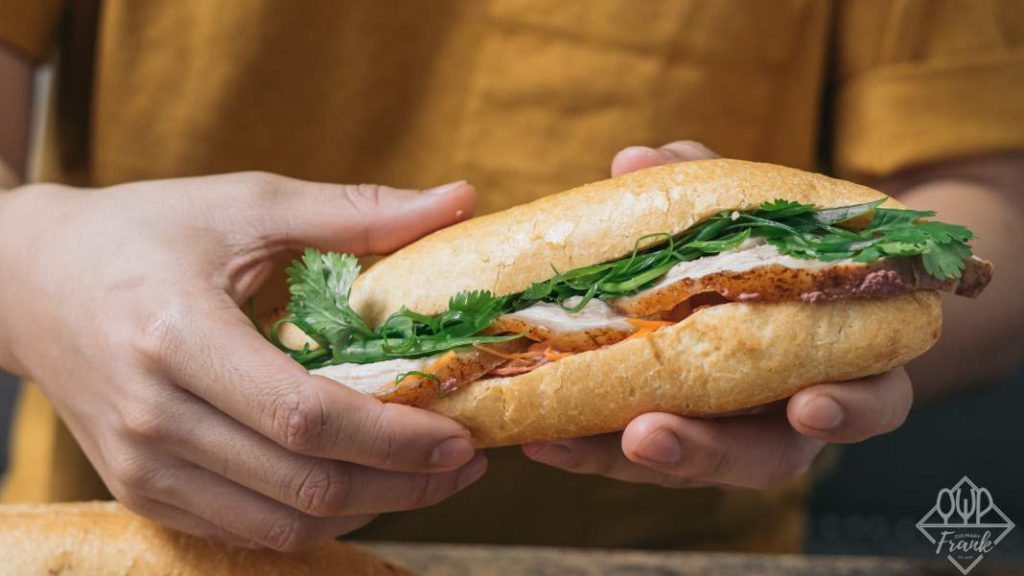 A hand holding a sandwich  Description automatically generated