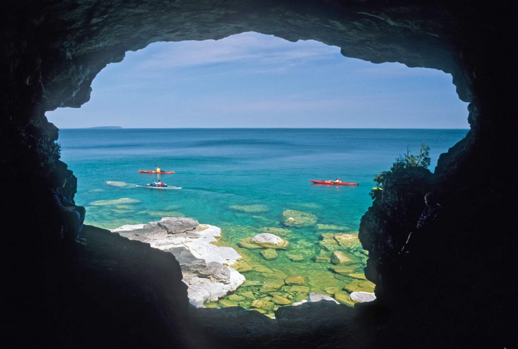 View of kayakers on Georgian Bay from Little Fern Cave, Bruce Peninsula National Park. © Parks Canada / D.A. Wilkes